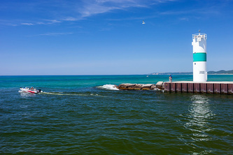 speed boat drives past the end of the pier and lighthouse