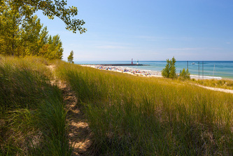 wide view from under tree looking out at Lake Michigan beach and pier with lighthouse