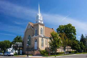 yellow brick church with white steeple in downtown Pentwater, Michigan