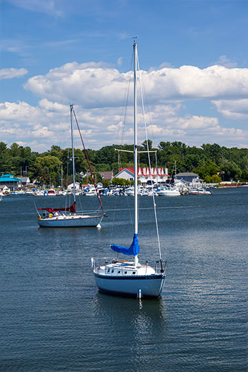sunny day, two sailboats docked in the harbor