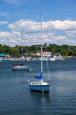 two anchored sailboats on calm summer day in Pentwater harbor