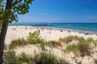 wide view of beach at state park with pier, beach-goers and Lake Michigan